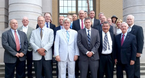 Business leaders flank McAlpine just before getting on the bus. Click to enlarge